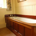 The House of Glenmuick wood trimmed bath tub for guests to relax.